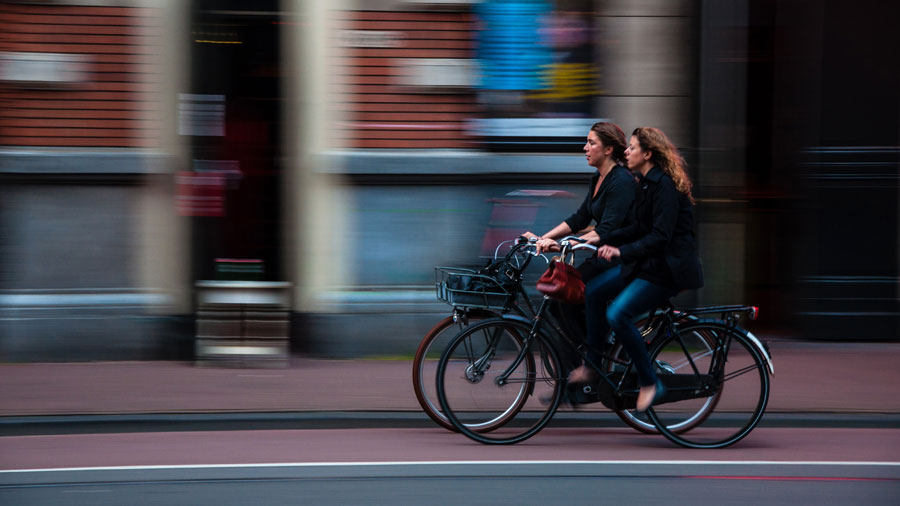 Two women cycling in an urban area