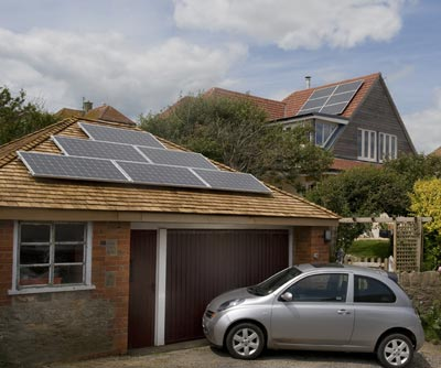 Electric car charging by garage with solar panels