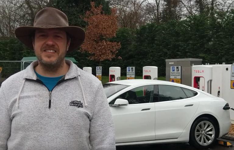 Jon Launder with a Tesla electric car