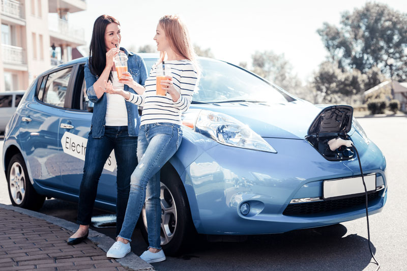Two friends by blue electric car