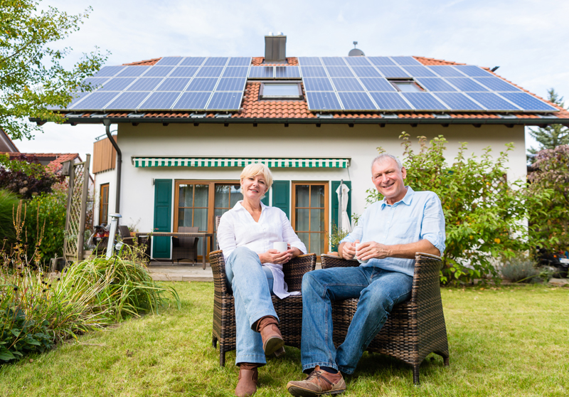Couple sitting outside bungalow with solar panels on roof