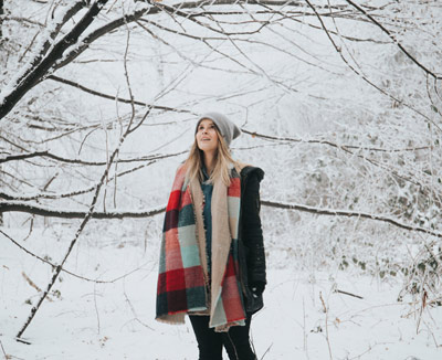 Woman in warm clothing standing in the snow